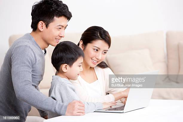 Young family surfing the net with laptop