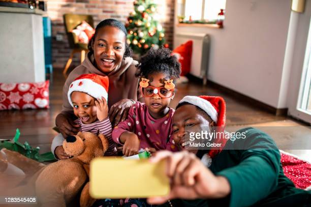 young family taking a selfie during christmas - holiday stock pictures, royalty-free photos & images