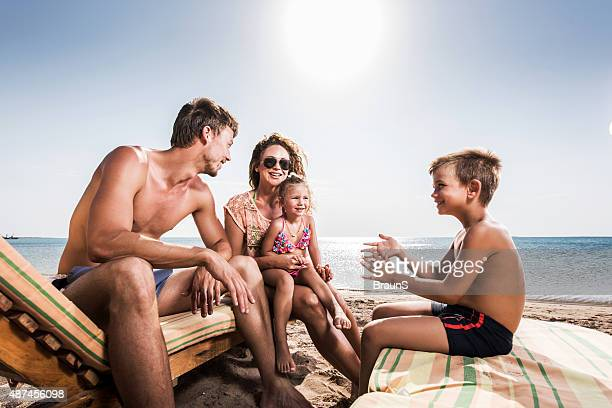 Young family talking on a deck chair at the beach.