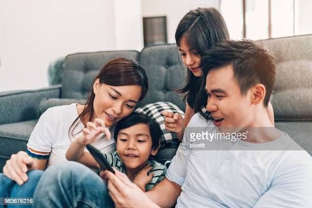 young family texting at home - south east asia stock pictures, royalty-free photos & images