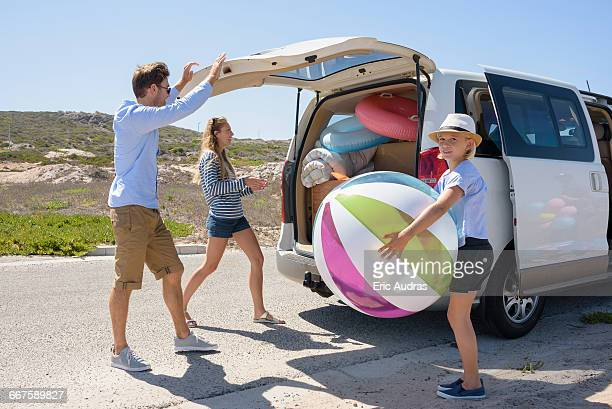 Young family unloading beach gears from car