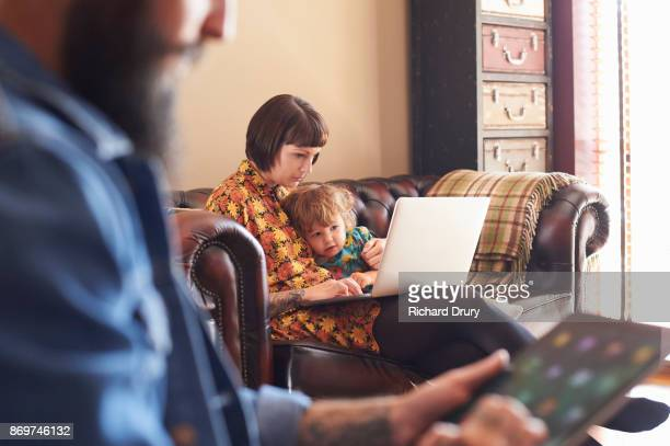 Young family using a laptop and digital tablet in their living room