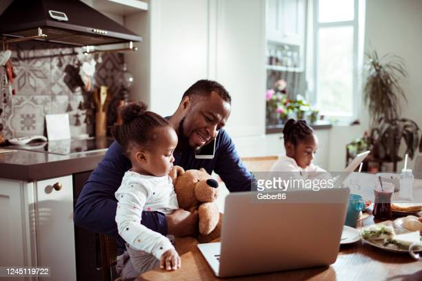 young family using a laptop during breakfast - home office stock pictures, royalty-free photos & images