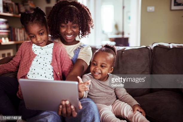 young family using a tablet - african ethnicity stock pictures, royalty-free photos & images