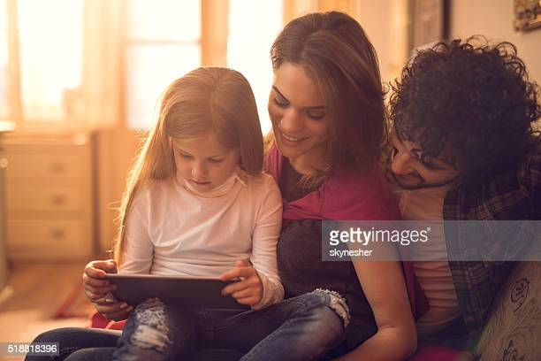 Young family using digital tablet together at home.