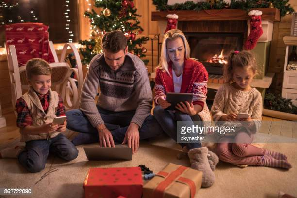 Young family using wireless technology on Christmas eve at home.