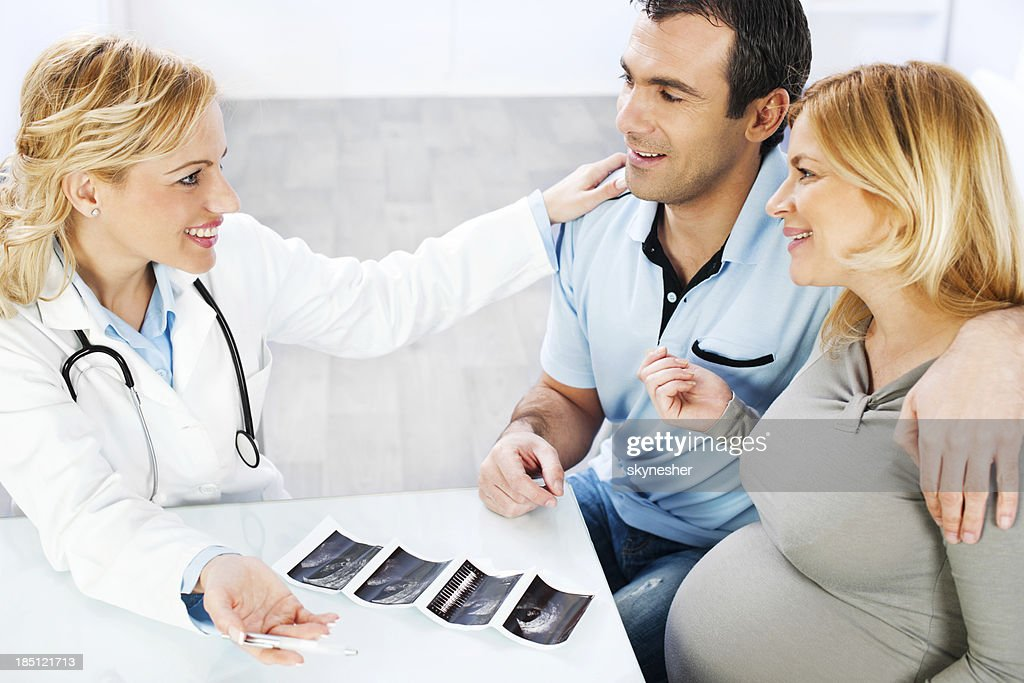 Young family visiting a doctor, looking at Ultrasound. : Stock Photo