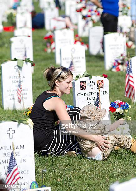 CONTENT] A young family visits a veteran's grave on Memorial Day Brittany Jacobs holds her son Chris near the grave site of her late husband...