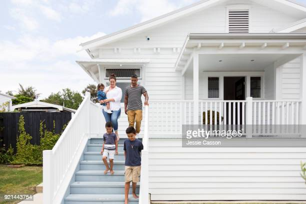 Young Family walk down steps in front of their home