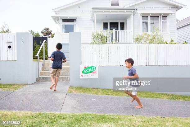 Young family walk in front of their new home with Sold sign