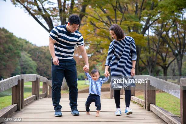 young family walking across the bridge in public park - in the park day 3 imagens e fotografias de stock