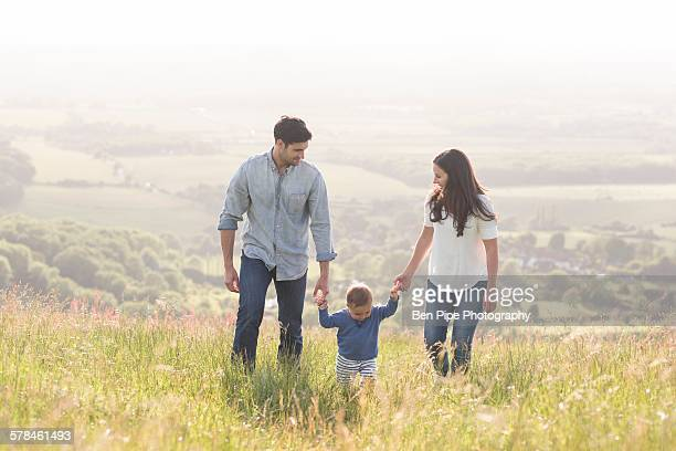 Young family walking in field, hand in hand