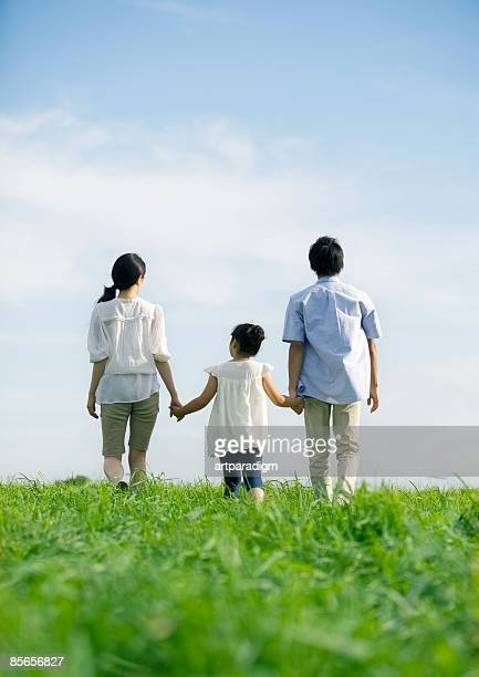 Young family walking on grass