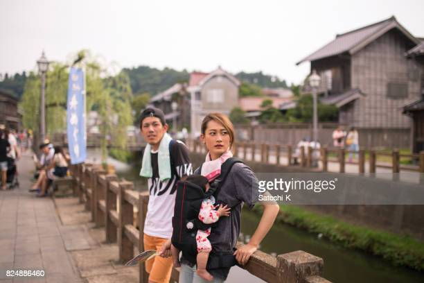 Young family walking on street in traditional Japanese town