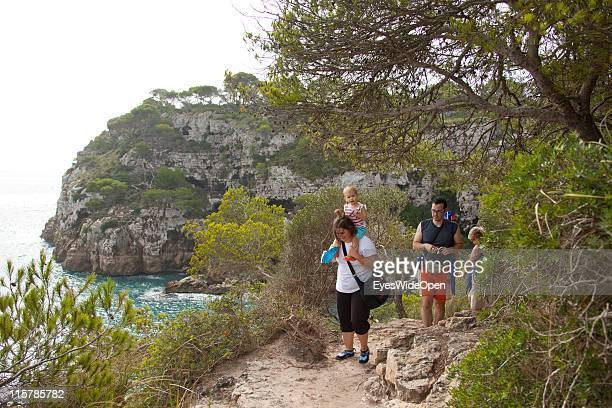 A young family walking on the historic bridleway Cami de Cavalls next to the beach of Cala Macarelleta on October 09 2010 in Menorca Spain Menorca is...