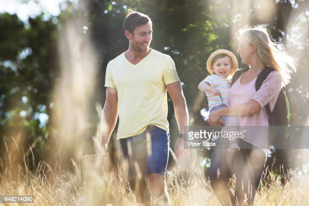 Young family walking through long grass in field with picnic