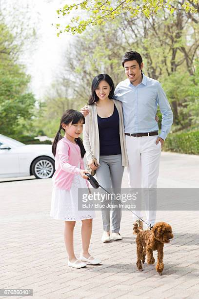 Young family walking with their pet dog