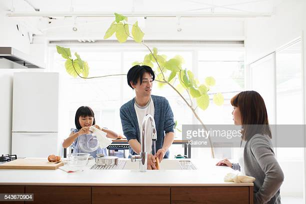 Young family washing dishes together in the kitchen