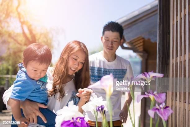 Young family watching iris flower on street