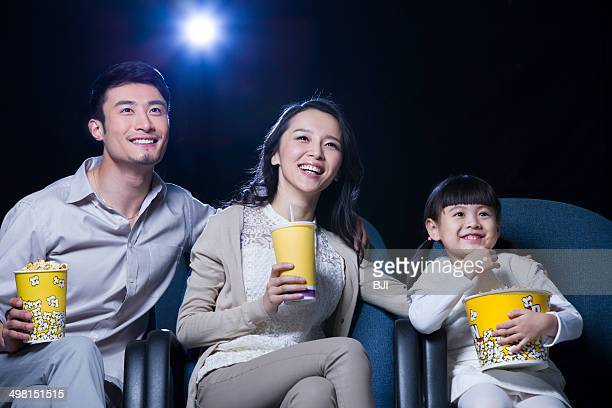 Young family watching movie in cinema