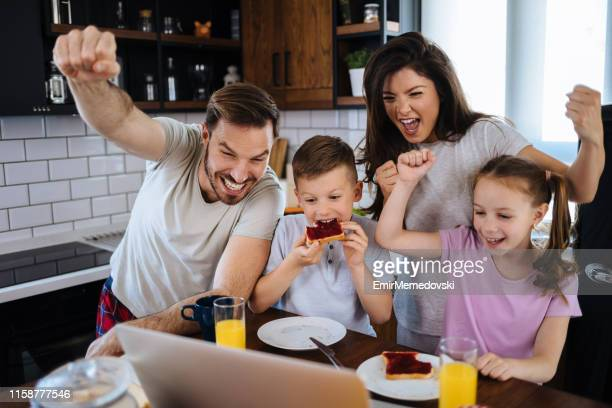 Young family watching soccer match on laptop in the kitchen
