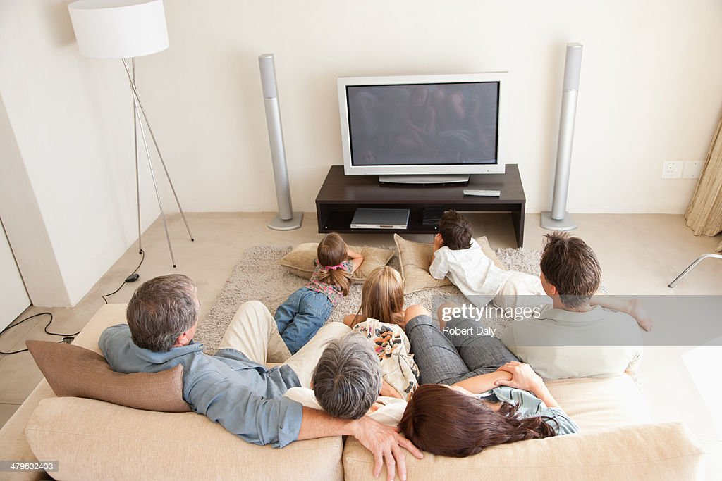 A young family watching television with grandparents : Stock Photo