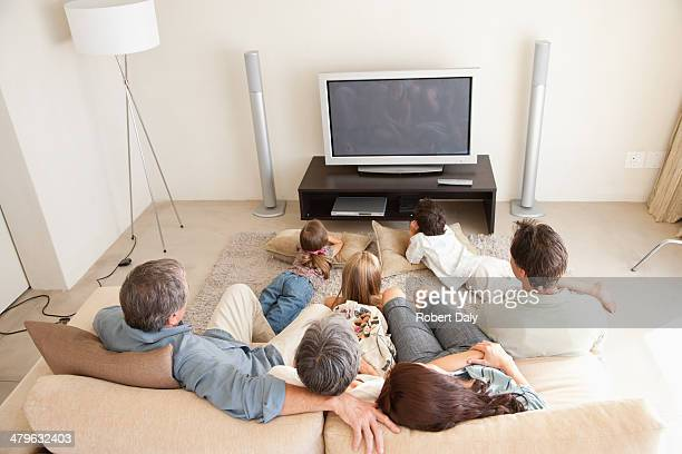 A young family watching television with grandparents