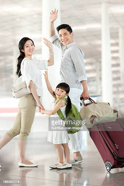 Young family waving goodbye at the airport
