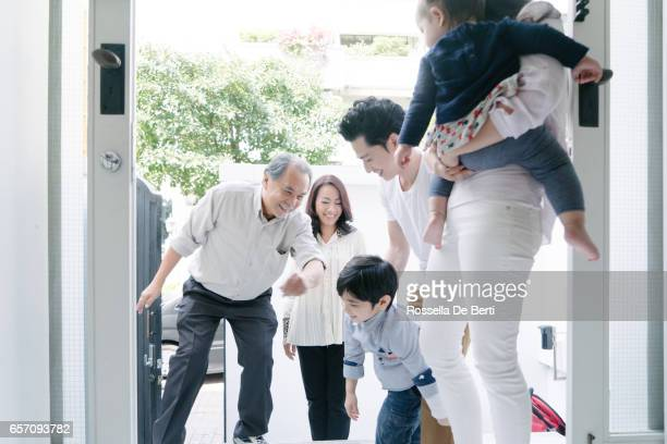 young family welcoming grandparents at home - visit stock pictures, royalty-free photos & images