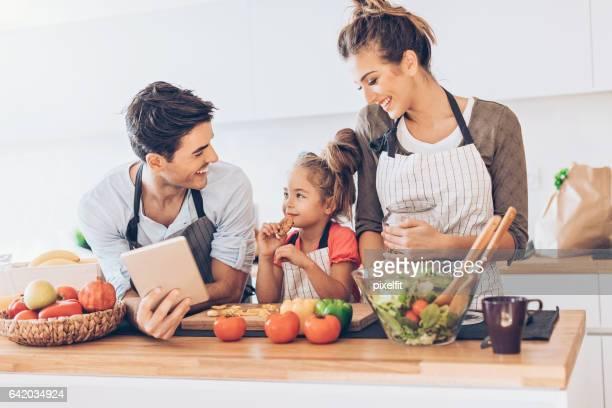 Jeune famille avec un enfant dans la cuisine