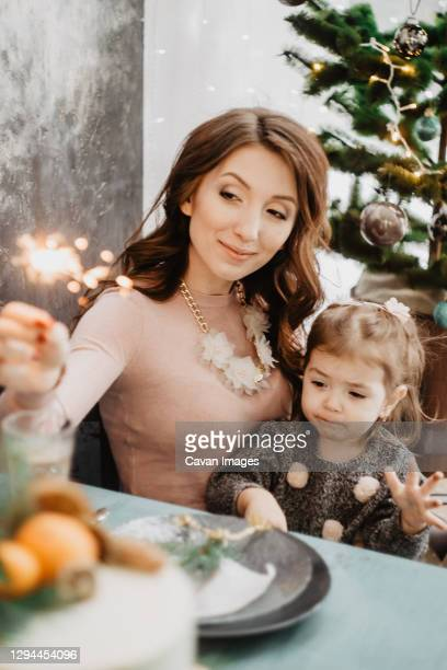 young family with a daughter in festive outfits at a served table with candles, garlands, sparklers and a cake near the christmas tree on new years eve - 25 29 years stock pictures, royalty-free photos & images