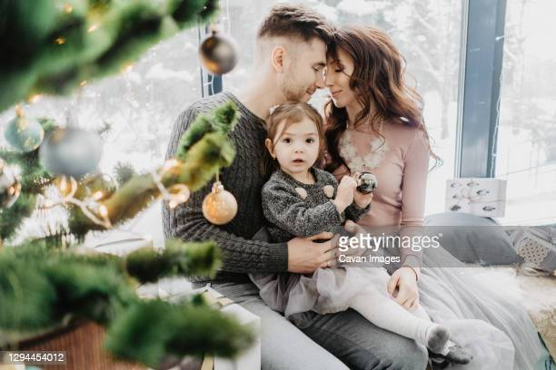 young family with a daughter in festive outfits with a garland near the christmas tree on new years eve - 25 29 years stock pictures, royalty-free photos & images
