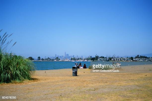 A young family with a stroller enjoys a picnic near the waters of the San Francisco Bay at Crown Memorial State Beach an East Bay Regional Park in...