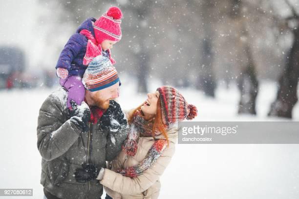 familia con niña divirtiéndose en la nieve - winter family fotografías e imágenes de stock