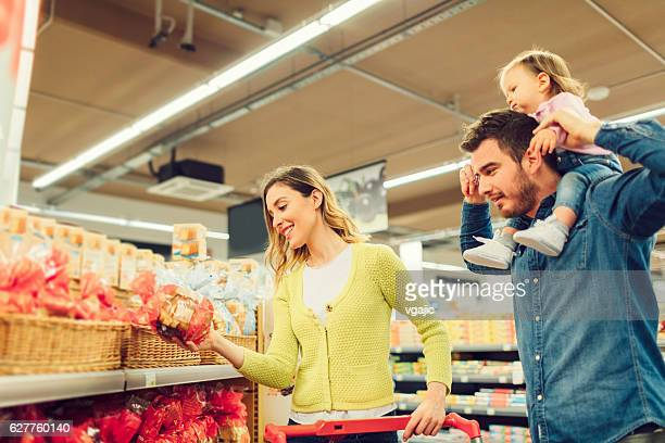 Young Family With Baby In Supermarket.