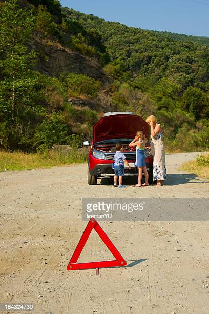 Young family with broken-down car and hazard triangle
