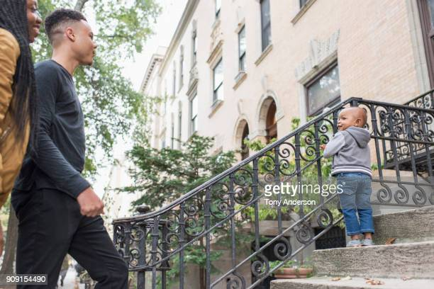 Young family with infant daughter in their city neighborhood stoop