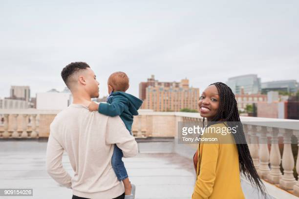 Young family with infant daughter on city rooftop