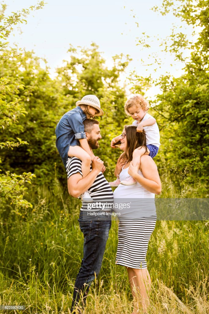 Young family with little daughters, carrying them on shoulders in sunny summer nature. : Stock Photo