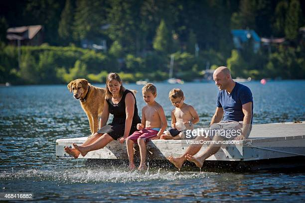Young family with pet sitting on dock by lake.