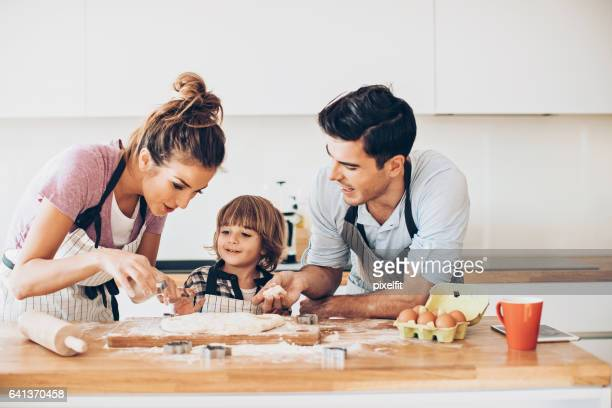 Young family with small child making cookies