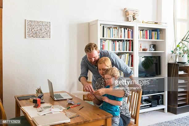 Young family with toddler son making paper plane
