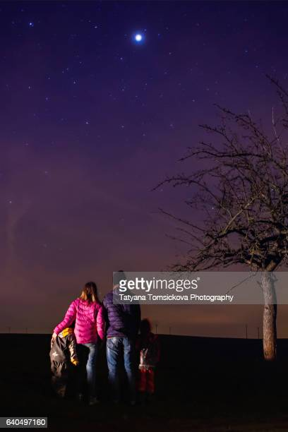 Young family with two kids contemplating the star night sky, springtime