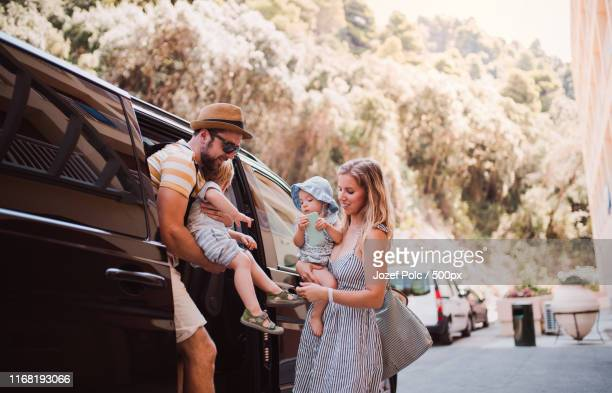 a young family with two toddler children getting out of taxi on summer holiday - 降り立つ ストックフォトと画像