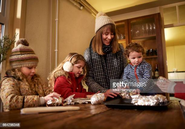 Young family wrapped up warm, preparing food