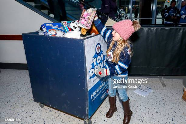 A young fan adds a toy to the donation bin prior to NHL action between the Winnipeg Jets and the Philadelphia Flyers for the Jets annual Toy Drive at...