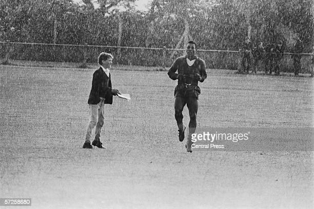 A young fan approaches Pele for an autograph while he is training in the pouring rain in Bolton in preparation for Brazils match against Portugal...