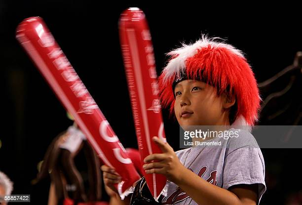 Young fan bangs his thunder sticks near the end of the game between the New York Yankees and the Los Angeles Angels of Anaheim during Game One of the...