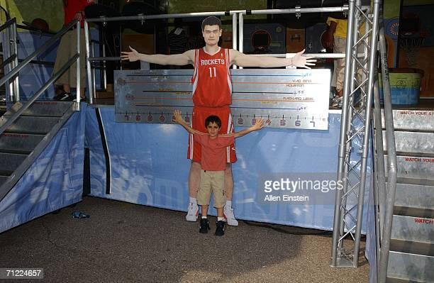 A young fan compares his arm span to that of NBA star Yao Ming at the NBA Rhythm 'N Rims Tour at the National Strawberry Festival on June 16 2006 in...