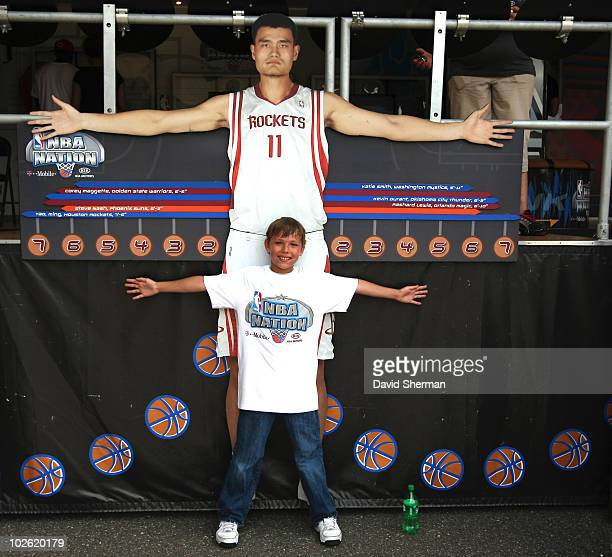 A young fan compares his armspan to a lifesize cutout of Yao MIng at NBA Nation interactive show at Taste of Minnesota outdoor festival at Harriet...
